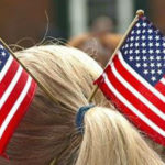 Blond ponytail with two USA flags coming out of blue rubber band