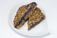bar cookie on white plate - brown oatmeal crusts with purple berry jam filling
