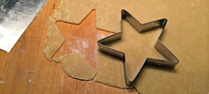 Cookie dough being cut in the shape of a star with a cookie cutter.