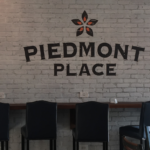 "The sign on the gray brick wall in the seating area reading ""Piedmont Place"", black chairs in front of wall"