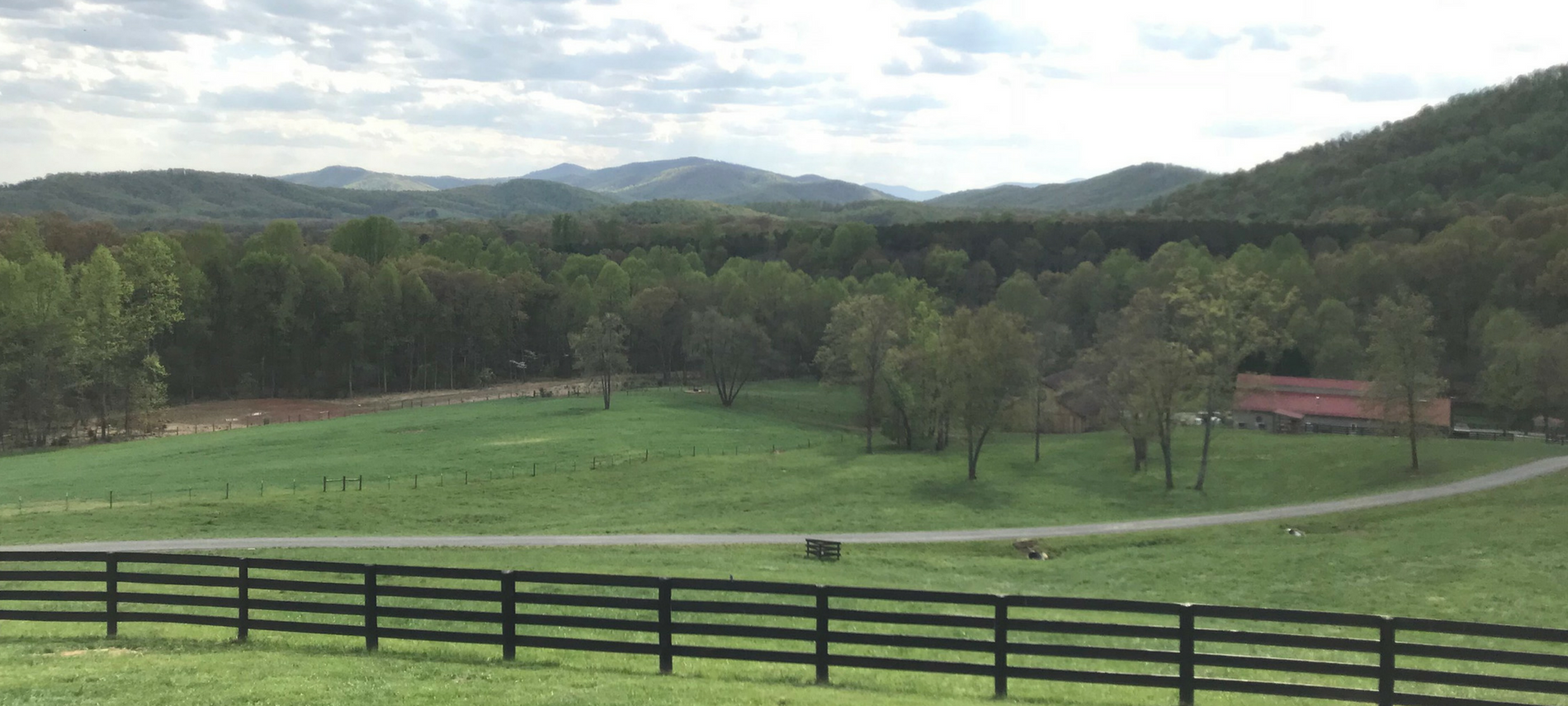green field, black horse fence, dirt road beyond fence and red roof low barn, lots of green trees in background and foothills of the Blue Ridge
