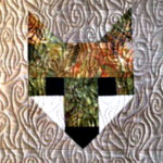 three fox heads in various colors (greens, browns, white, black) quilted on a beige-grey background