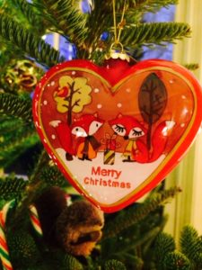 An ornament on a tree with small foxes in a winter scene reading Merry Christmas.