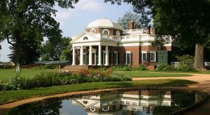 Thomas Jefferson's Monticello pictured behind a pond and lawn area.