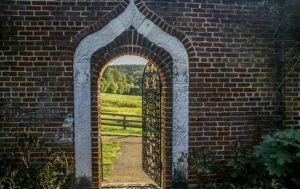 red brick wall with white arch opening to green field