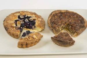 Two tarts on a white background - one topped with blueberries and one with pecans