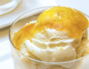 white ice cream in glass bowl topped with peach sauce