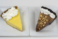 Two pieces of pie on two separate white plates - onepie yellow and the other chocolate