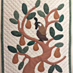 Beige quilt wall hanging with a brown pear tree with green leaves and brown pears plus a dark partridge on a cream background with green edging