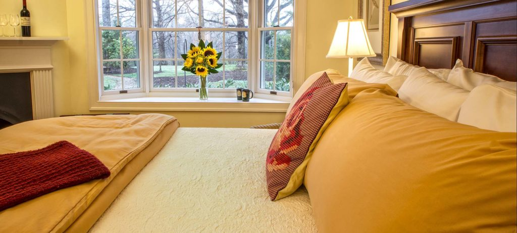 A view from one of the rooms at Foxfield Inn. A bed with beautiful mustard colored linens and sunflowers on the window sill.