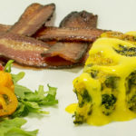white plate with bacon, tomato salad and vegetable frittata