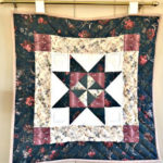 quilted wall hanging with blue flowered edges, blue & magenta star on white in center, hanging on a cream wall