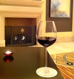 A wine glass on a table in front of a fireplace. The glass has red wine in it.