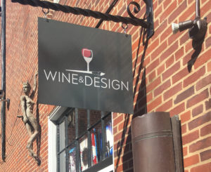 "black sign on a brick wall, white lettering for ""Wine & Design"" with a glass of red wine above the letters"