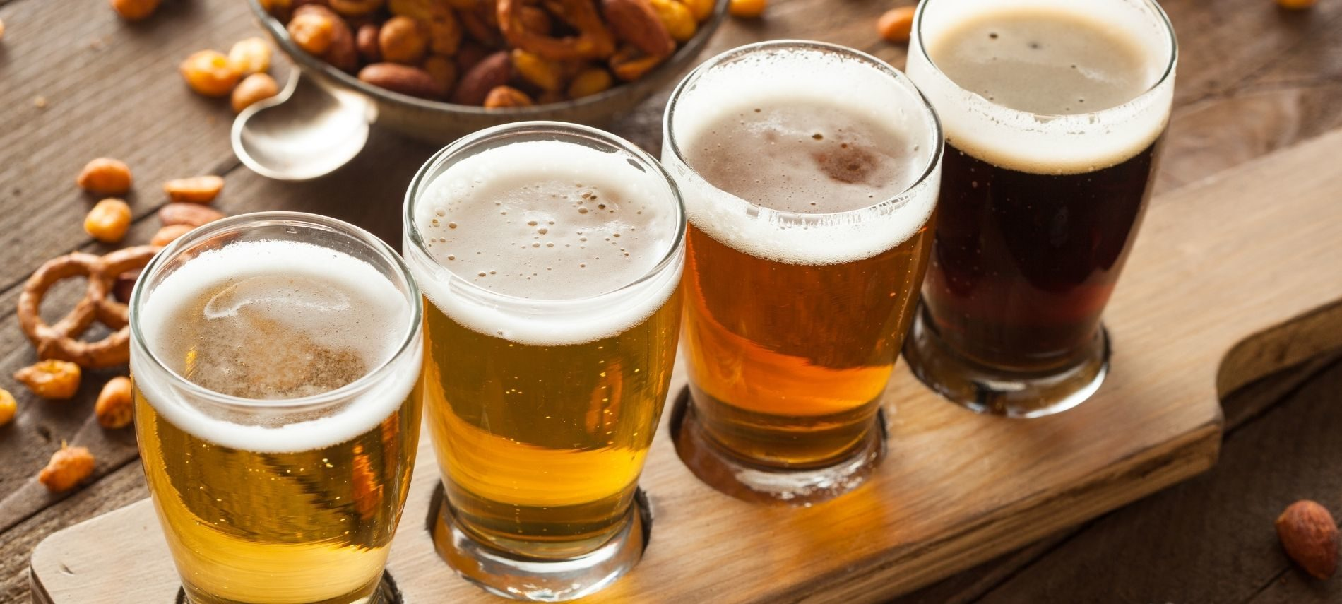 Flight of beer in different shades of amber surrounded by pretzels.