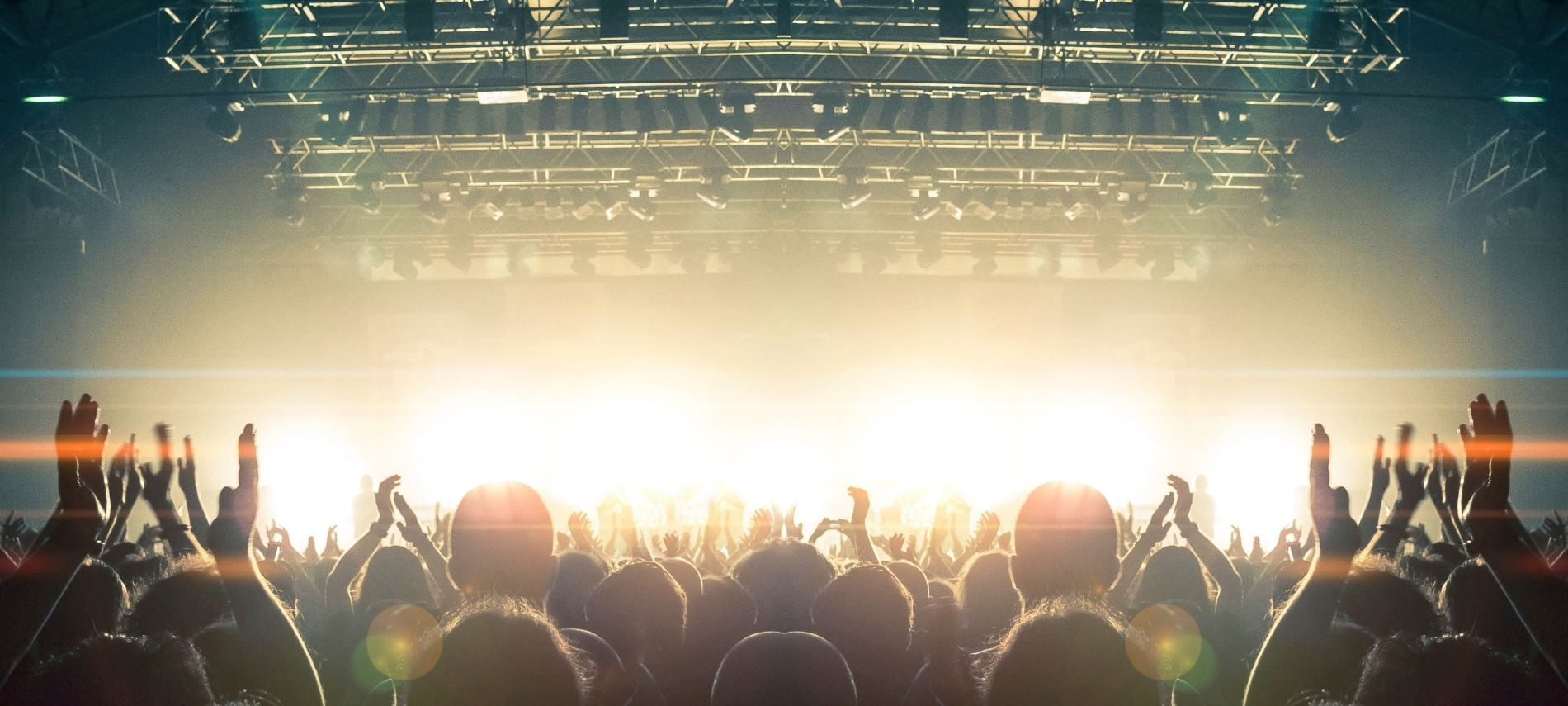 Silhouette of audience watching live concert with arms in the air