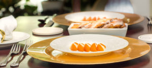 white plates on gold chargers with sliced apricots