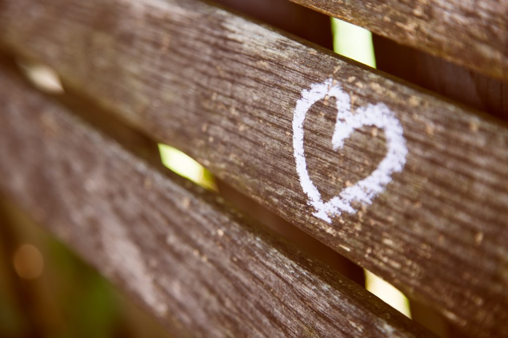 A white heart written in chalk on a wooden fence.