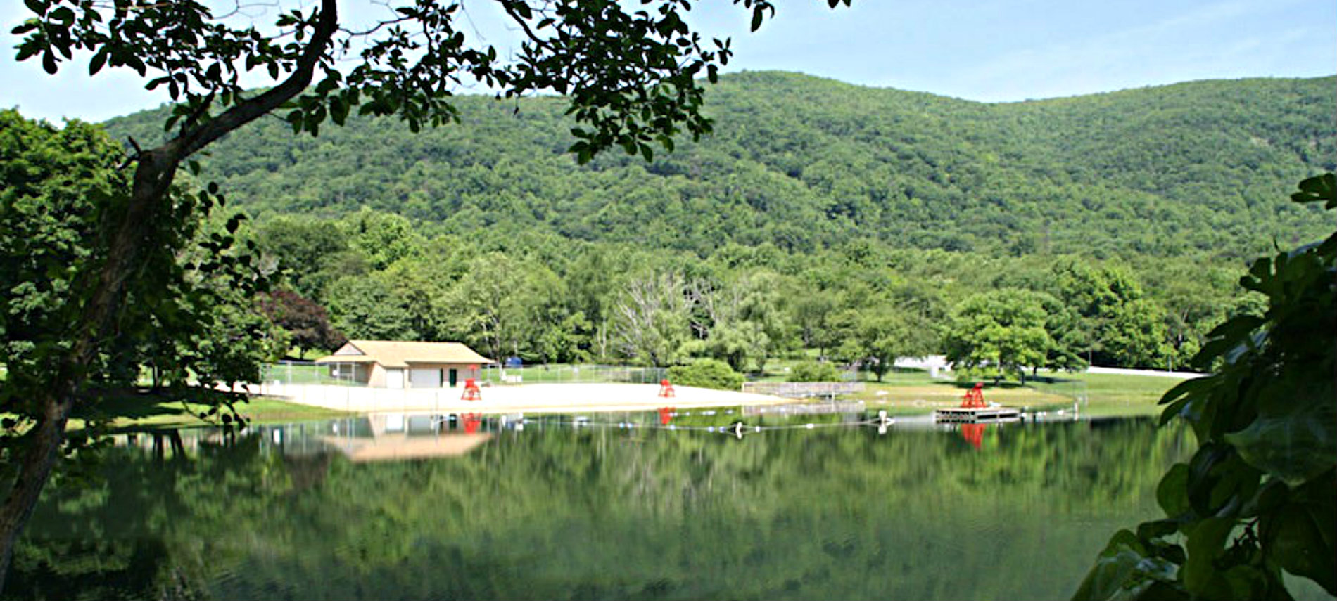 lake in foreground with green trees and white cabin in back
