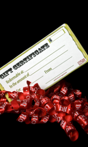 """A gift certificate with a holiday bow reading """"ho ho ho"""""""
